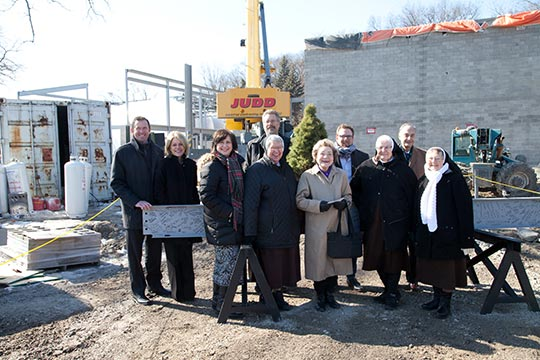 Dignitaries posing in front of beam and construction site
