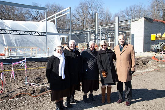 Other dignitaries posing in front of beam and construction site