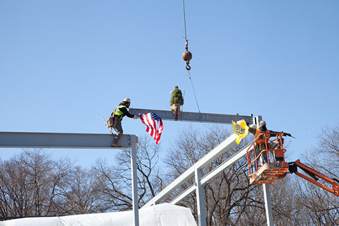 Beam being put into place by construction workers