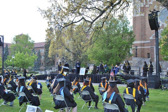 Graduates seated outdoors during ceremony