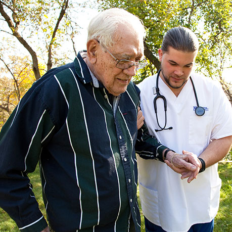 Male Nursing Student helping along an elderly gentleman outdoors