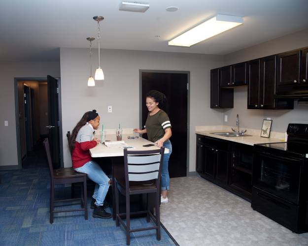 two students talking in the kitchen, featuring a breakfast bar